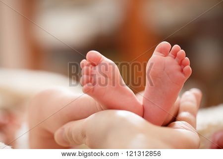 Mother holds in his hands a small baby foots