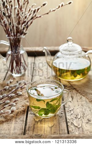 Eucalyptus tea with leaves in transparent cup and teapot