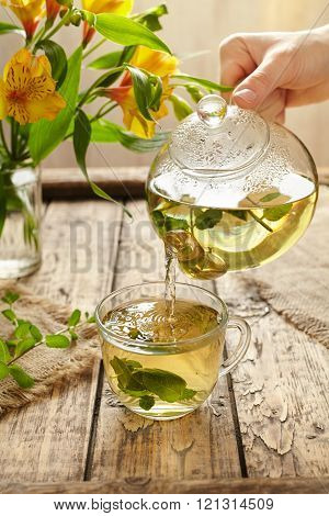 Sage tea pouring in glass transparent cup from teapot