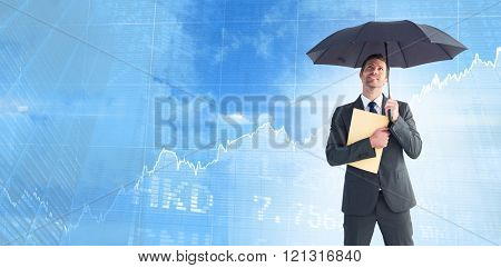 Businessman sheltering under umbrella holding file against stocks and shares