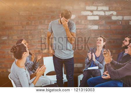Rehab group applauding delighted man standing up against brick wall