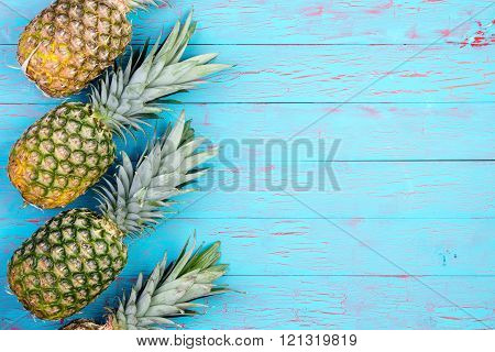 Slanted Pineapples Arranged On Wooden Table