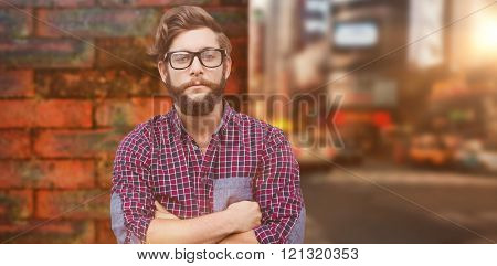 Confident hipster wearing eye glasses with arms crossed against wall of a house
