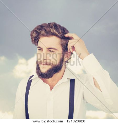 Hipster scratching head while thinking against beautiful blue cloudy sky