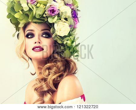 Beautiful model with flower wreath on his head . Makeup smoky eyes .