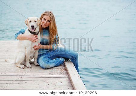 Schönes Mädchen mit ihrem Hund am Liegeplatz in der Nähe von Meer