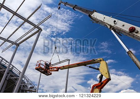 High Elevated Cherry Picker With Worker On Construction Site.