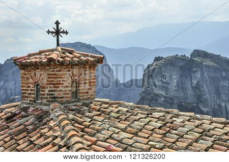 Orthodox cross in one of the monasteries in Meteora in the background the mountain massif. Greece.