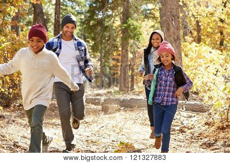 African American Family Running Through Fall Woodland