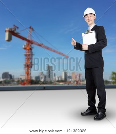 Asian Engineer In Black Suit And White Haelmet Holding Check List Standing On Construction Site