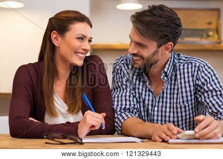 Young happy couple at home after pay payment of bills. Young couple having a brief conversation on accounts. Happy young couple smiling and looking at each other in casual.