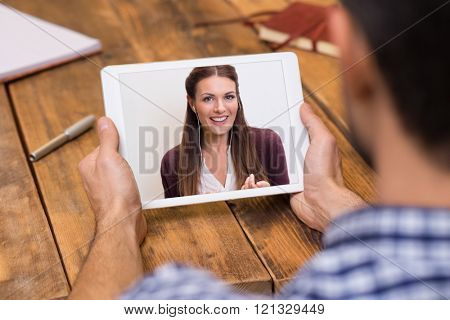 Closeup of a woman talking through video chat on tablet. Young man communicating with his girlfriend on tablet in video chat. Man looking at screen of tablet and talking with a girl through webcam.