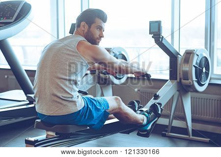 Rowing at gym. Side view of young man in sportswear doing rowing in front of window at gym and looking away