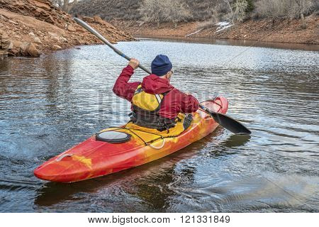 paddling colorful kayak on a calm river or lake  - recreation concept