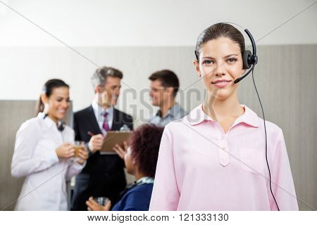 Confident Female Customer Service Representative Standing At Off