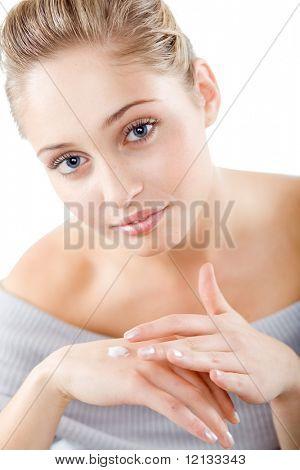 Young beautiful woman applying hands cream and looking at camera