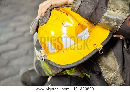 Firefighter Holding Yellow Helmet At Fire Station