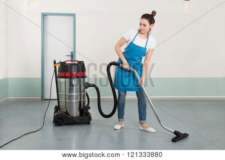 Young Female Janitor Cleaning Floor With Vacuum Cleaner