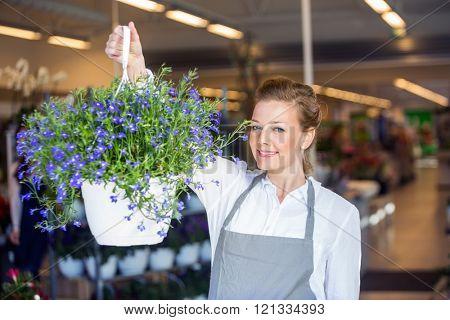 Female Florist Holding Flower Plant In Shop