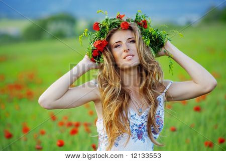 Girl with long beautiful hair wearing floral wreath over fresh grass and flowers