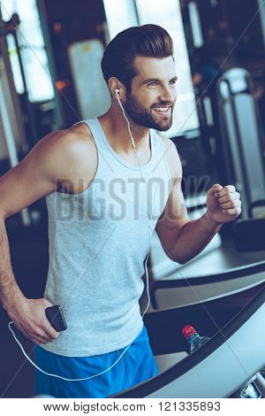 Five miles with pleasure. Cheerful young handsome man in headphones looking away with smile while running on treadmill at gym