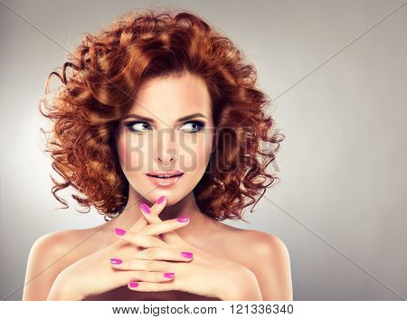 Beautiful model  with  red curly hair and pink manicure