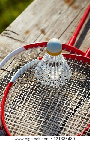 Badminton racquets with plastic shuttlecock on a bench close-up