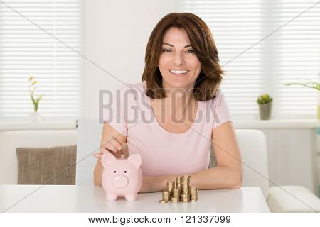 Smiling Woman Inserting Coin In Piggybank