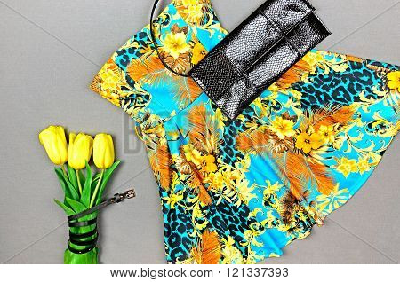 Dress With Floral Print, Yellow Tulips And Black Clutch On Gray Background