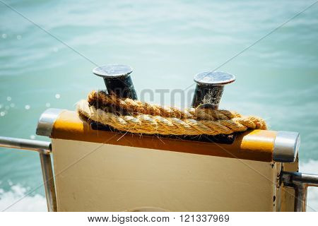 boat bollard (bitt) with rope against water background