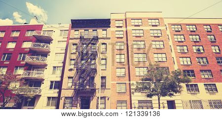 Vintage toned photo of New York building with fire escape ladder, USA.