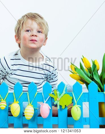 Llitle boy lying behind an artificial blue fence with Easter decoration