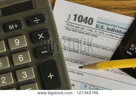US tax form 1040 with pencil and calculator