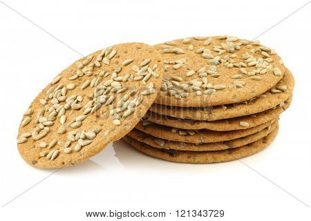 stacked crispy spelt crackers with sunflower seeds on a white background