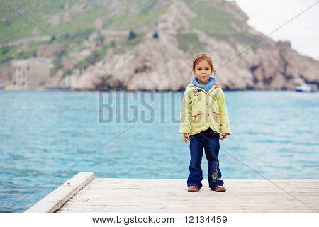 Cute Child am Liegeplatz in der Nähe von Meer im Herbst