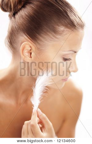 Hermosa mujer tocando la pluma a su piel limpia sana closeup sobre blanco