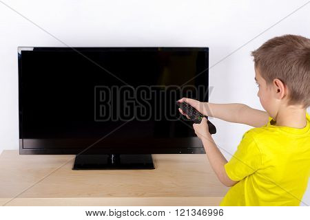 The young boy turning off the television