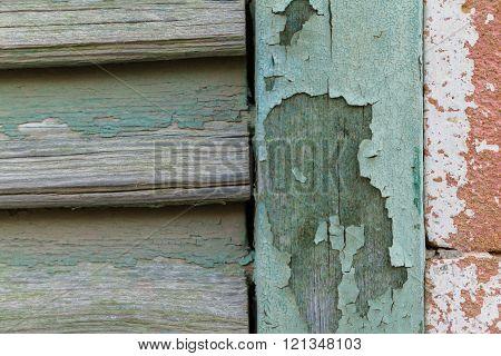 Cyan peeling paint window wood planks and pink brick wall