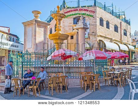 JERUSALEM ISRAEL - FEBRUARY 16 2016: The medieval stone drinking fountains on the Muristan Square surrounded by the tables of the local tavern on February 16 in Jerusalem.