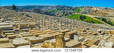 The ancient Jewish Cemetery on the Mount of Olives with the medieval walls of Jerusalem and its modern districts on the background Israel.