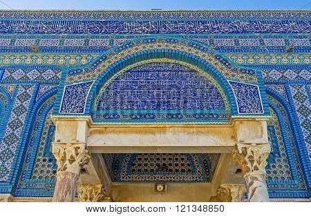 JERUSALEM ISRAEL - FEBRUARY 16 2016: The side entrance canopy of the Dome of the Rock decorated with the old arabic calligraphy islamic patterns on the glazed tiles and carved stone pillars on February 16 in Jerusalem.