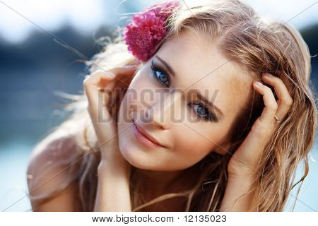Portrait of young beautiful smiling female with flowers in her wet hair