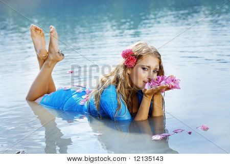 Portrait of young beautiful woman resting in water smelling rose petals