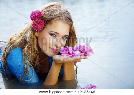Portrait of young beautiful woman resting in water smelling rose petals closeup