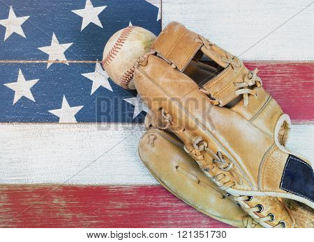 Old Worn Baseball Mitt And Ball On Faded Boards Painted In American National Flag Colors