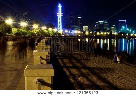 Baku Bulvar at night with people blurred due to movement