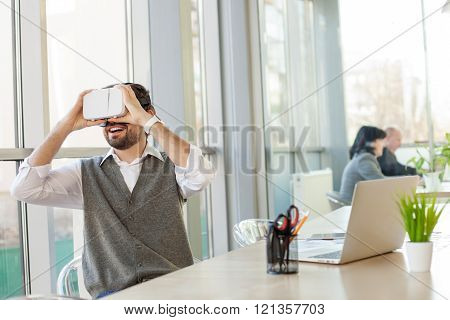 Cheerful male worker is using modern technology