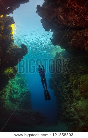 Free diver gliding in the cave of tropical sea