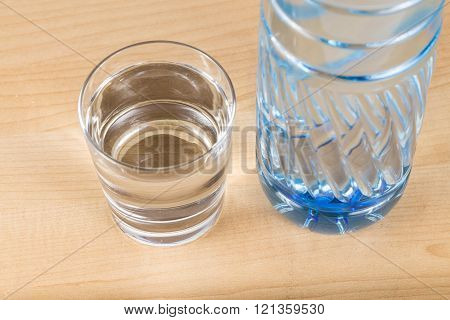 Refreshing natural mineral water in plastic bottle with transparent glass