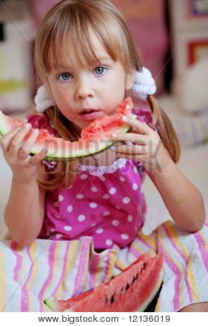 Funny child eating watermelon closeup